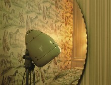 Melinda's Room by Leanora Olmi, 2015. An image of the reflection of a mirror showing the wall and part of a bed of a bedroom. The wallpaper is green and has a pattern of horses, and in front of it we see the head of a green old-fashioned lamp.